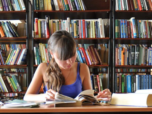 Школьница в читальном зале библиотеки